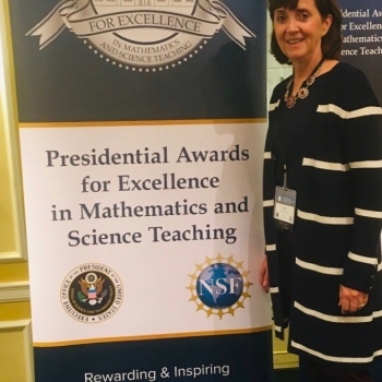 Mrs. Holt-Taylor stands by the Presidential Awards for Excellence in Mathematics and Science Teaching banner in Washington, D.C.